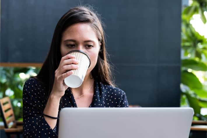 Mujer navegando en un equipo portátil y tomando café